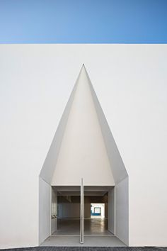 Deep triangular and flat-topped arches are punched through the bright white walls of this community centre by Manuel and Francisco Aires Mateus