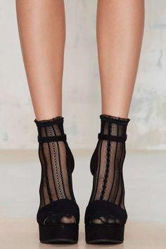 Gambaletti e sandali neri con tacco alto.