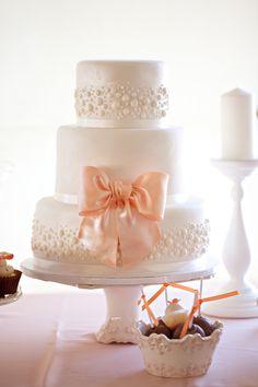 Bolo de casamento branco, de três andares, com detalhes de pérolas de pasta americana e enfeitado com um laço de fita de cetim salmão. Foto: Amanda K.