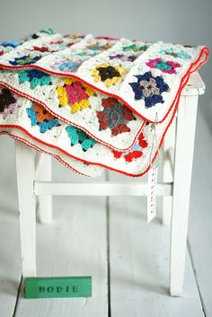 Crochet blanket made of colourful little squares on a white background