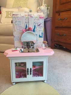 Made an American Girl bathroom sink/cabinet for Emily. Started with a unfinished cabinet from hobby lobby and added porcelain cabinet knobs for the feet. Cut a hole in a decorative board big enough for an old stainless soap dish to fit in. Added more cabinet knobs and a broken top off a soap dispenser to look like a faucet. I guess if it wasn't broken she could have running water? Maybe later. Added accessories from various AG/OG sets and a round placemat for a rug.