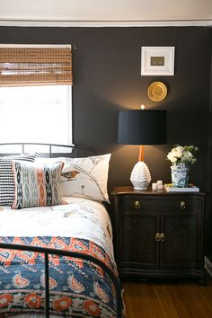 "Sneak Peek: Jessica McKay and Christopher Van Buskirk. ""Our guest bedroom is small so I wanted it to feel cozy. We painted it in Sherwin-Williams Urbane Bronze, added a contrasting bright bedding from Dwell Studio, and placed a vintage textile from ebay at the foot of the bed. I paired new black drum lampshades with vintage white lamps I found at a thrift store for bedside lighting."""
