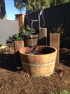 Rustic water feature using an old well pump, wine barrel and railway sleepers