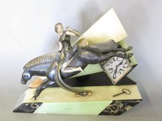 ART DECO ONYX & MARBLE MANTEL CLOCK:  A cast bronze figure of a woman riding a leaping horse, wearing a dress painted with gold arrows. Mounted on a geometric marble and green and white onyx base, with a diamond shape clock face