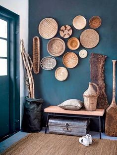 Blue painted entry with a cork IKEA bench | woven baskets as wall decorations | simple sisal rug | boho minimal hallway