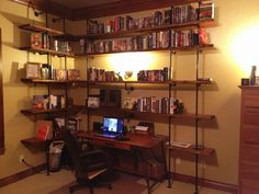 """Pipe bookshelves built around a desk. Uses inexpensive 2x12 boards distressed to look old. 1/2"""" pipes make strong enough shelves to hold a lot of novels!"""