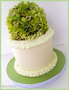 A small buttercream cake topped with a gumpaste hydrangea sphere along with matching piped hydrangea cupcakes.