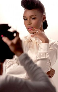 Janelle Monae poses in her signature hairstyle, and a silky white blouse as the new face of CoverGirl