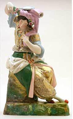 Teapot #489  Figurine, lady with black hair, wearing a pink head-dress; seated on green base; green and   pink overskirt over gold speckled harem pants; bodice, matching pants, has blue sleeves.