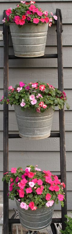 Antique ladder and galvanized steel buckets filled with flowers