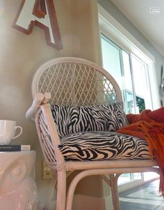 Dining Room Thrifted Rattan Chair makeover with spray paint and black and white zebra print fabric at thehappyhousie