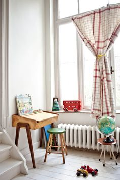 Globe lamp. Retro desk and chairs. Heavy Curtain. White floor and walls. Retro decorations. Red and green accent