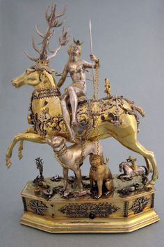 "Eltz Castle ""Diana Riding a Stag"", mechanical drinking game on wheels, silver, partly gold-plated, Joachim Friess, Augsburg around 1600 Diana was wound up and then moved around the table. Wherever she stopped, the man had to empty the stag and the woman had to empty the dog, both of which were filled with wine. Both cups were connected with short chains, thus forcing the drinkers to get close."