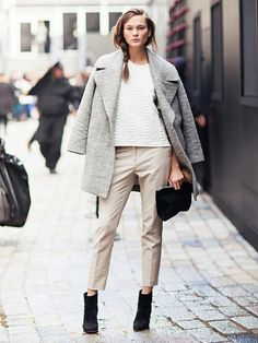 A white top is worn with cream pants, black booties, black clutch and a grey coat.