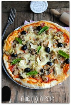 Pizza à base de sauce tomate, jambon mozzarella, artichaut, champignons, olives noires, basilic.