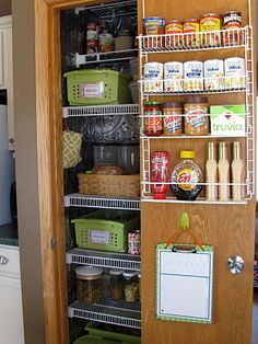 organized pantry with over-the-door shelves. Clipboard has the shopping list. Small bag hanging in closet is for clips (for chips, etc.)