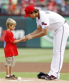 Texas Rangers starting pitcher Yu Darvish (11) hands an autographed baseball to Cole Wollis, 7, of Mansfield, Texas, on the pitcher's mound prior to the start of a baseball game against the Oakland Athletics on Sunday, July 1, 2012, in Arlington, Texas. ?(AP Photo/John F. Rhodes)  game 80