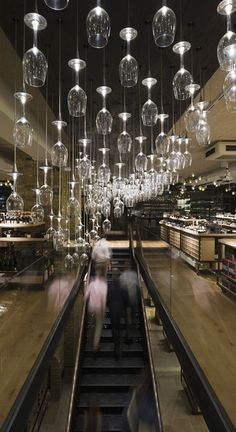 Hedonism Wines by Speirs + Major: Created from upended wine glasses mounted at varying heights, the organic sculptural form is inspired by the contour lines of a vineyard.  Individual LEDs illuminate each glass, forming a dazzling three-dimensional effect. #wine #retail #ceiling