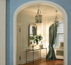 Entryway pale blue and cream damask wallpaper, blue-green chinz drape with ruffled edge, eggshell blue in next room looking in, wrought iron table and caned window glass ... AUSTIN FOSTER - The Enchanted Home