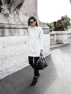 Modern Legacy wears a turtleneck tunic, skinny jeans, ankle boots, Givenchy duffle bag, and black sunglasses
