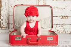 LOVE the vintage suitcase, old wooden wall that's white, with the pop of red!