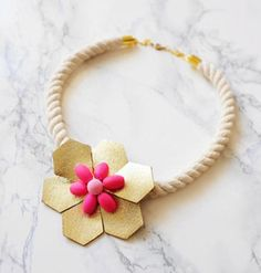 "The combination of humble white-cotton rope, flashy gold leather, and neon pink bead ""petals"" gives this handmade flower necklace its unique appeal. #etsyjewelry"