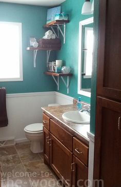 Beautiful and inexpensive bathroom update. Really unique and modern feel in this bath now!   white, teal, bathroom, shelves, storage, color, paint, painting, chair rail, wainscoting, trim, casing, modern, unique, ideas
