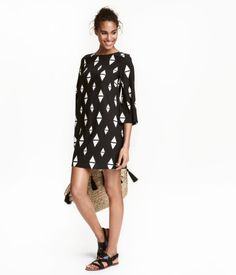 Sort/Hvid. Kjole med let vidde i blød, vævet viskose med trykt mønster. Kjolen har trekvartlange ærmer med vidde samt åbning og knap i nakken. Uden for.