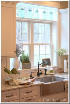 Our Kitchen Window with lots of light and gorgeous set of blue mason jars displayed.  From the blog:  Finding Home.