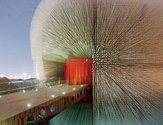 """Thomas Heatherwick - """"Seed Cathedral""""  """"comprises 60,000 transparent acrylic rods, each 7.5 meters long, piercing a wooden frame. By day, the rods bring light to the interior, but at night they glow from LEDs. The ends of the rods contain seeds from the Germplasm Bank of Wild Species at the Kunming Institute of Botany, which gives the pavilion its nickname, the """"Seed Cathedral."""" When a breeze comes off the Huangpu River, it animates the pavilion, setting the translucent tentacle"""