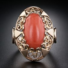The hallmarks tell us that this sizable and fanciful coral cocktail ring hails from Krakow, Poland, circa 1963! An elongated oval cabochon coral, with a rich orange color, is happily ensconced in a 14 karat rose gold mounting, elaborately adorned all over with open heart motifs. The coral measures 17.90 millimeters by 10 mm. The ring measures 1 1/8 inch by about 7/8 inch across.