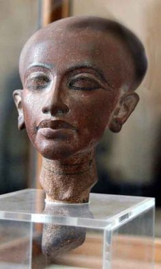 Statuette head composition representing one of Akhenaten's daughters with the classic Amarna elongated face and skull, thick lips and prominent thighs. Cairo Museum, Egypt. akhenatens daughter 2
