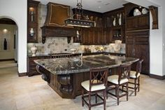 Dark wood, dark marble, giant awesome kitchen