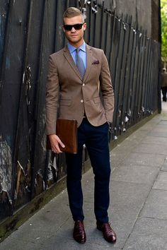 Acheter la tenue sur Lookastic: https://lookastic.fr/mode-homme/tenues/blazer-chemise-de-ville-pantalon-chino-chaussures-richelieu--cravate--lunettes-de-soleil/520 — Pochette de costume á pois pourpre — Chemise de ville bleu — Pantalon chino bleu marine — Blazer brun — Chaussures richelieu en cuir bordeaux — Pochette en cuir brune — Cravate géométrique bleu marine — Lunettes de soleil brun foncé