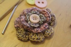 A crocheted flower brooch. The two available colours are shown in the picture - pink and green variegated yarn with a pink button and green yarn