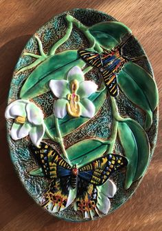 Modeled as an oval shaped tray with a mottled green and brown bark ground profusely decorated with plump green orchid leaves, large white orchids and a swallowtail butterfly at each end. Bears all the