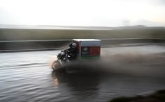 Two men on a motorcycle drive through a flooded street near the Moroccan capital Rabat