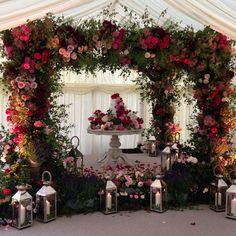 A rose bower surrounds an incredibly elegant wedding cake. Flowers by Agent F #littlebookforbrides #weddingcake #weddingflowers