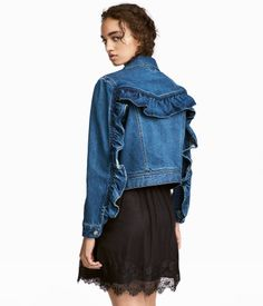 Denim blue. Jacket in washed denim with a ruffle at front and back. Collar, buttons at front, and side pockets.