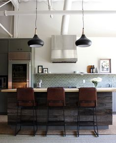This room has two neutral colors, brown and white. Which are accented with a real blue on the backslash of the kitchen.