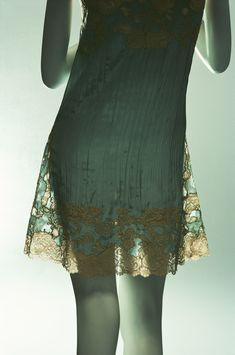 "Chemise - It is an undergarment worn by women. They were now much shorter and more narrow, following the silhouette of women's dresses. This particular one is made of blue silk ""crêpe de Chine"" with lace insertion."