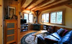 Den in an open-floor plan home. Includes exposed wood beams and plank ceiling and wood-plank chair rail.