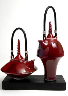 Ceramics by Melanie Brown at Studiopottery.co.uk - 2006. Variation Two - Sang de boeuf teapots on a beech block