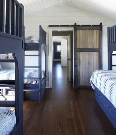 A wood plank barn door on rails opens to a white and blue cottage bunk room boasting three blue bunk beds matched with blue ladders and dressed in white and blue bedding. Awesome Woodworking Ideas, Woodworking Projects That Sell, Woodworking Garage, Woodworking Joints, Woodworking Furniture, Woodworking Workshop, Woodworking Crafts, Bunk Beds With Drawers, Bunk Beds Built In