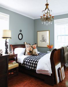 Tommy Smythe's Bedroom - lovely chandelier, interesting and well-placed art, stunning pillow is the perfect contrast to the checkered black and white blanket.  Rich mahogany wood sleigh bed perfect against grey green walls.