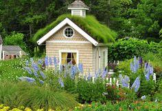 Em meio a um jardim, esta she-shed possui telhado verde e tem charme de sobra