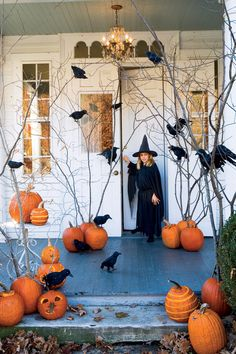 For a killer entrance, perch ravens on bare branches with pumpkins as their base.  - GoodHousekeeping.com  This will be so cool for Halloween!