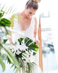 The addition of a glossy monstera leaf gives this cascading orchid #bouquet a tropical spin! | Photography By: Alicia Thurston Photography | WedLuxe Magazine | #WedLuxe #Wedding #luxury #weddinginspiration #luxurywedding #floral