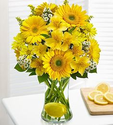 A bright bouquet of yellow Gerbera daisies and/or sunflowers, alstroemeria, daisy poms and more, designed in a striking glass gathering vase -- with an added twist of a real lemon.