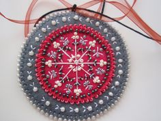 pretty beaded and embroidered felt ornament. Beads. Embroidery. The link is bad. Google blocked it for me, so there is no source.